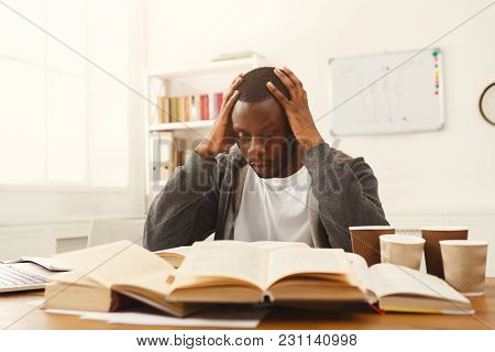 Tired African-american Student Studying At Working Table. Exhausted Male Student Preparing For Exams