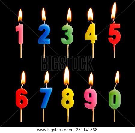 Burning Candles In The Form Of Figures (numbers, Dates) For Cake Isolated On Black Background. The C