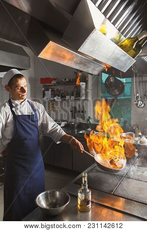 Male Chef Cooking Medium Beef Steak Flambe. Healthy Exclusive Food Prepared At Professional Kithen,
