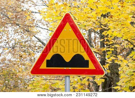 Uneven Road Sign On Yellow Autumn Leaves Background