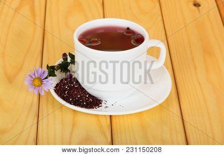 Cup Of Hot Tea, Crushed Fruits Of Dry Dog-rose On Saucer, Against Background Of Beige Wooden Table