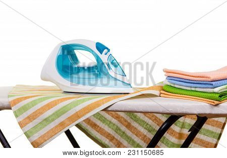 Stack Of Clean Towels And An Iron On An Ironing Board Isolated On White Background