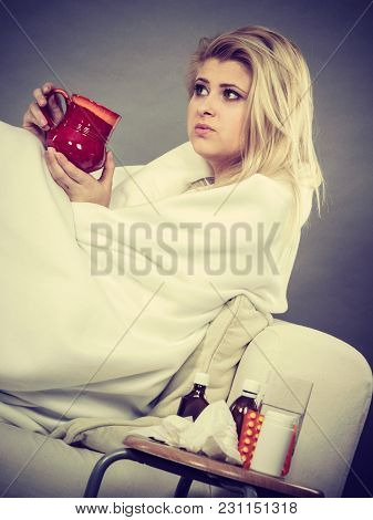 Sickness, Seasonal Virus Problem Concept. Woman Being Sick Having Flu Lying On Sofa Holding Mug Cup