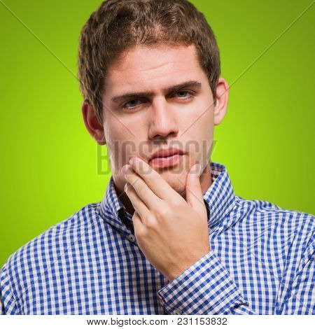 Young Man Thinking against a green background