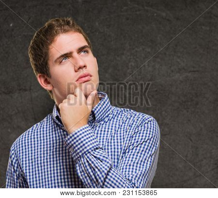 Portrait Of Young Man Thinking against a grunge background