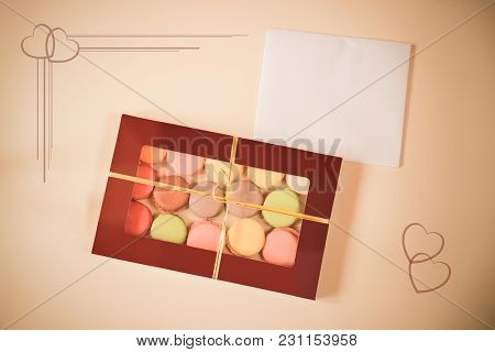 Macaroons In Gift Box And Card On Beige Background