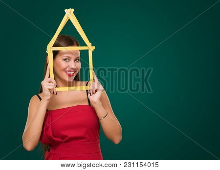 Happy Young Woman Looking Through House Frame against a dark green background