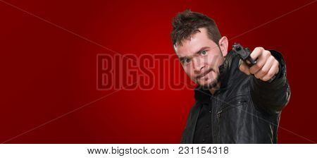 mad man pointing with gun against a red background