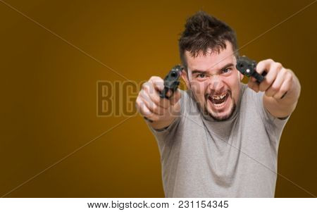 angry man aiming with guns against an orange background
