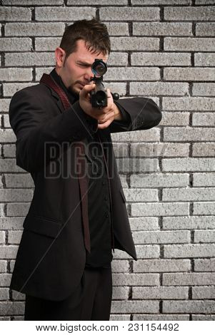 Man aiming with rifle against a brick wall