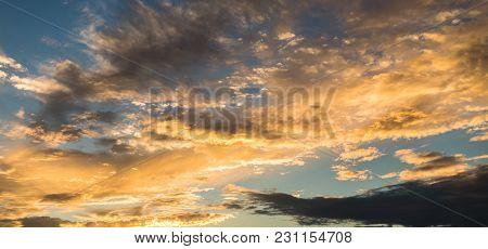 Beautiful Panoramic Golden Sky Cloudscape Sunset. Setting Sun Illuminates The Clouds.