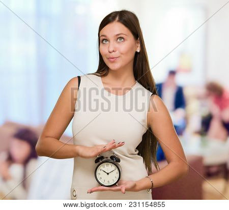 Woman Holding Alarm Clock and looking up against an abstract background