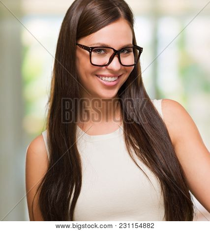 Portrait Of A Young Woman Holding Stopwatch And Wearing Specs, indoor
