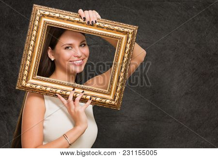 Portrait Of A Young Woman Holding Frame against a grunge background