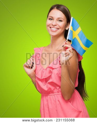 Portrait Of A Young Woman Holding Swedish Flag against a green background