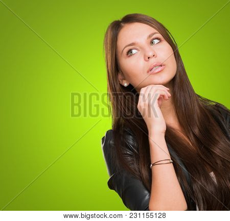 Young Woman thinking against a green background