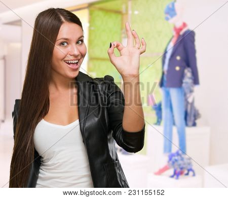 Portrait Of Happy Young Woman Gesturing Okay Sign in a clothes shop