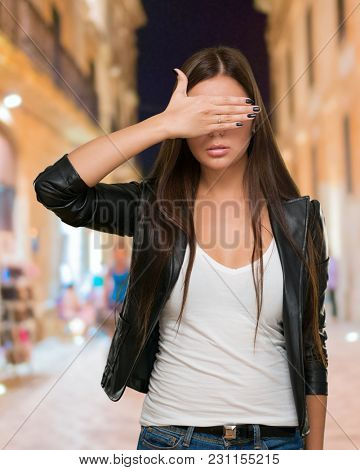 Young Woman Covering Her Eyes against a street background