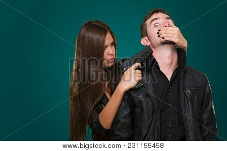 Criminal With A Gun Threatening Young Woman against a dark green background