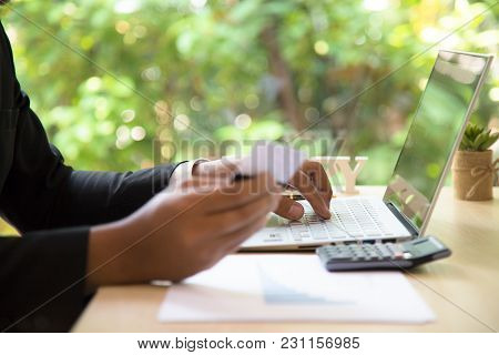Rear View Of Modern Businessman Hands Holding Credit Card Typing Numbers On Computer Keyboard While