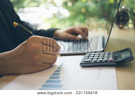 Blurred Of A Businessman Writing On Charts Paper At Workstation. Modern Business Man Writing On Char