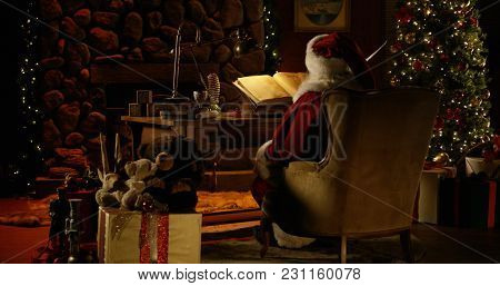 Santa Claus Works At His Desk, Surrounded By Christmas Decorations
