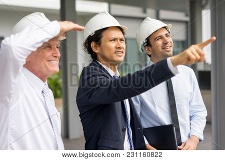 Middle Aged Tensed Man In Helmet And Suit Pointing At Neighboring Buildings To Content Partners. Con