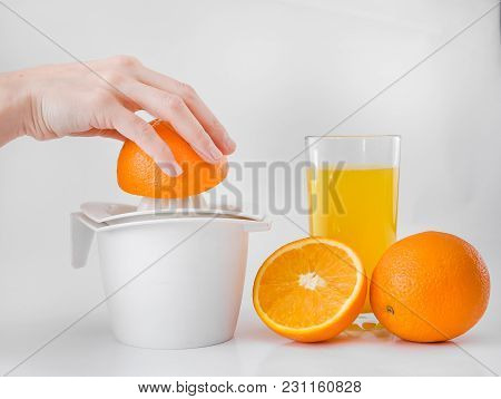 Woman In The Kitchen Squeezes Juice From The Orange By Hand