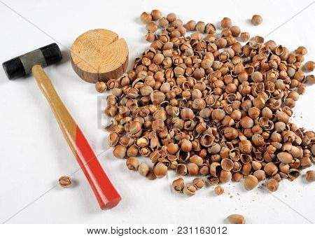 Crack Hazelnuts With A Hammer On The White Table