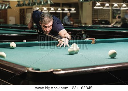 Billiards Player Plays Billiards Aiming At The Ball
