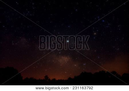 The Milky Way Rising Over The Horizon In Summer Night Sky With Light From A Nearby Town At The Horiz