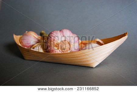 Pink Garlic Heads In A Natural Wooden Container With Gray Background