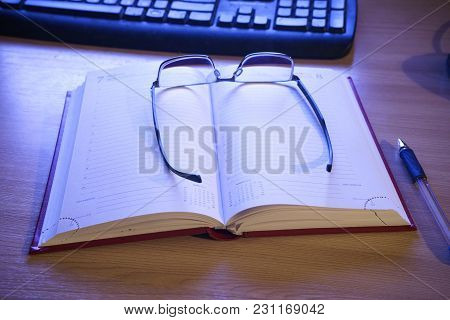 Glasses And A Pen On An Open Book For Notes On The Table Next To The Keyboard And Mouse Lighted By A