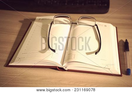 Glasses On An Open Book For Notes And A Pen Lying On A Table Next To The Keyboard