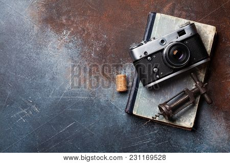 Vintage camera and wine corkscrew over old book. Top view with space for your text