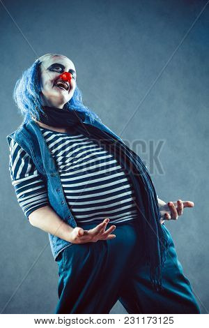 Scary Ugly Clown On The Studio Background. Mad Circus Troupe.