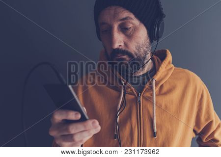 Man Listening To Music From Smartphone On Headphones, Adult Caucasian Male With Cap And Yellow Hoodi