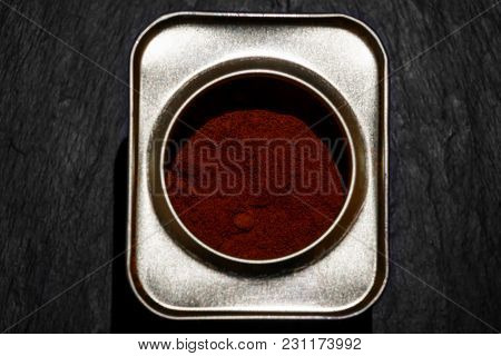 Smoked Paprika Powder In Metal Can View From Top In Black Stone Background