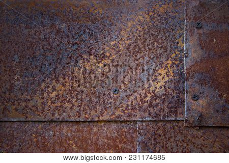 Textured Background Of Old Rusty Sheets Of Iron. The Joints Between The Sheets Are Visible
