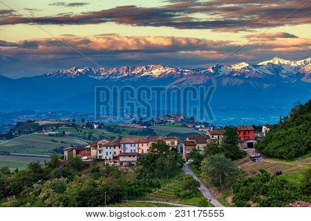 View of rural houses, hills of langhe and mountains ridge on background in Piedmont, Northern Italy.