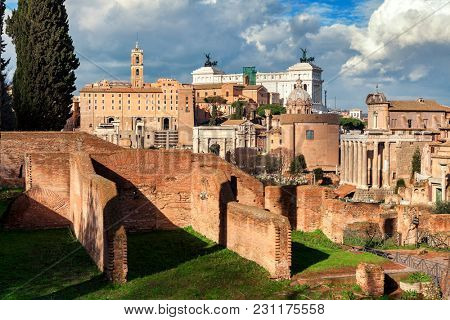 View of ruins of antique Roman Forum as Victor Emmanuel II altar on background in Rome, Italy.