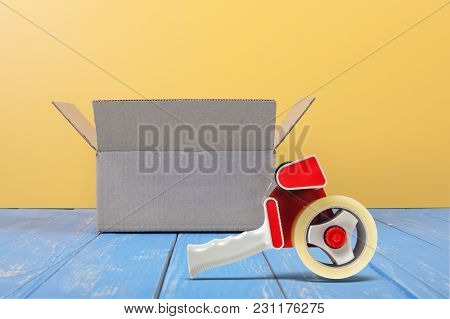Postage And Packing Service - Open Package And Tape Dispenser Front View On A Blue Wood And Yellow W