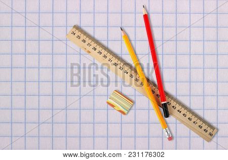 Stationery - Wooden School Ruler, Eraser And Two Graphite Pencils On A School Paper Background