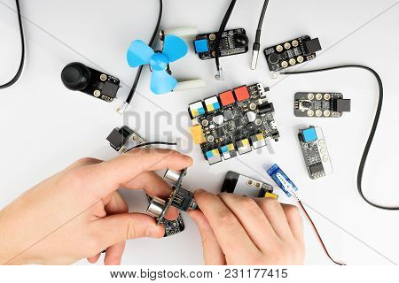 Robot  Building  Kit Above View. Hands Assembling Electrical Boards
