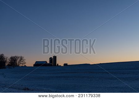 Winter Scene Of A Dairy Barn And Silos On A Hilltop At Sunrise With Blank Area Above.