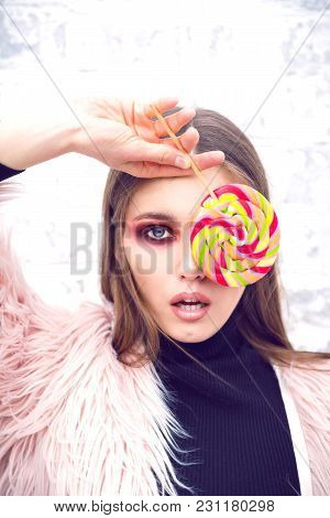 A Girl With A Multicolored Lollipop. Girl In Casual Clothes. Brick Wall Background. Gloomy Makeup. F