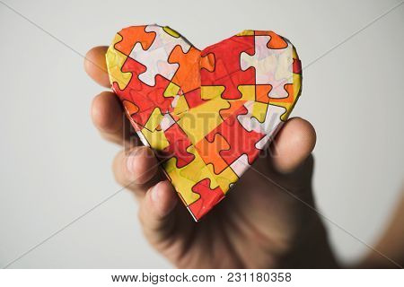 clousep of a young caucasian man holding a heart patterned with many puzzle pieces of different colors, symbol of the autism awareness