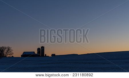 Dairy Farm On A Hilltop At Sunrise In The Winter. Blank Area Above For Copy.