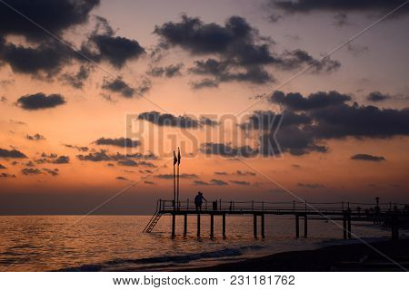 Summer Romantic Background On Sunset. Couple Of Lovers On The Pier Is Embracing. Love Story