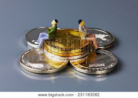 Coins Of Different Crypto-currencies With The People Sitting On Them. Bitcoin, Dash, Ripple, Ethereu